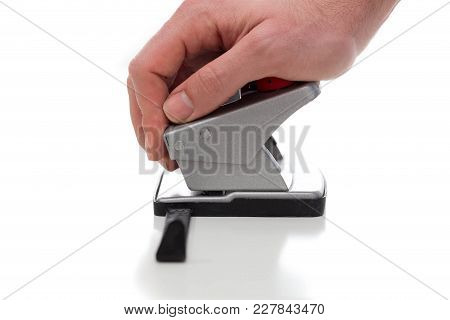 Puncher Used By A Hand Against A White Background