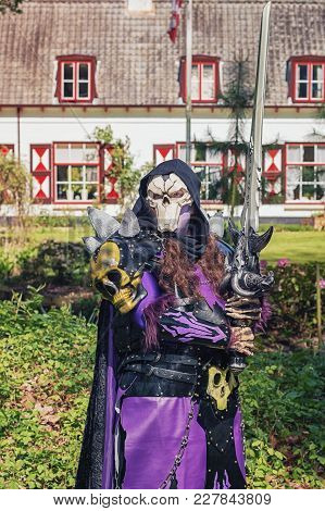 April  19, 2014, Haarzuilens, The Netherlands: Evil Man With Skull Mask And Huge Sword Poses During