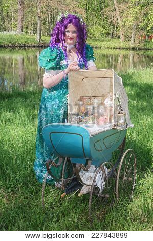 April  19, 2014, Haarzuilens, The Netherlands: Dressed Woman With A Purple Wig And Antique Pram Fill