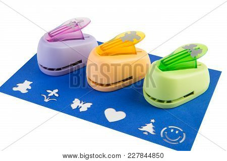 Three Curly Stapler On Blue Paper, White Background, Isolated