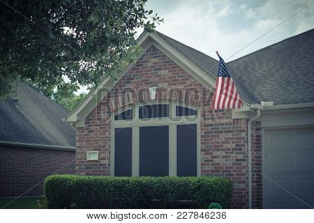Facade Of American Home Proudly Displaying Flag