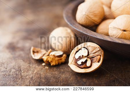 Bowl On An Old Wooden Table, Half Of A Walnut Kernel In The Form Of A Heart