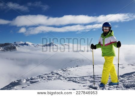 Young Skier With Ski Poles At Top Of Snowy Mountains At Sun Winter Day. Caucasus Mountains In Haze.