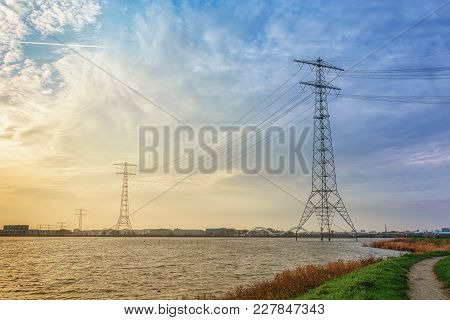 Electricity Poles In The Lake Buiten Ij With The Amsterdam District Ijburg In The Background.