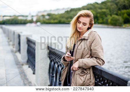 Attractive Blonde Girl Walking Along The Promenade And Listening To Music With Headphones