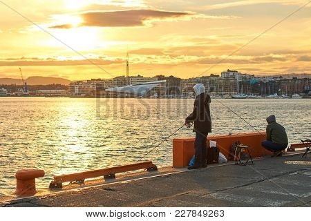 Oslo, Norway: Apr 25 2017 - Fishermen Fishing On The Quay Near The Akershus Castle At The Evening.