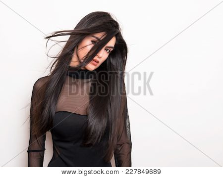 beautiful young woman with long black hair posing on grey background with copy space