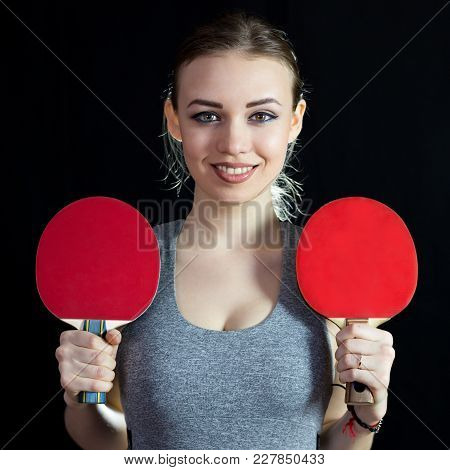 The Athlete Holds In Her Hands Two Table Tennis Shoes On A Black Background.