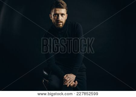Bearded Man Wearing Black Looking Unemotionally At Camera On Black Background Of Studio.