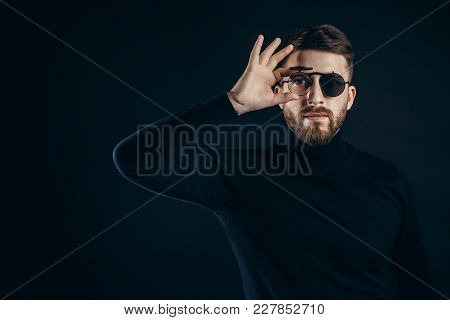 Portrait Of Handsome Bearded Man In Black Turtleneck Looking At Camera In Flip Sunglasses On Black.