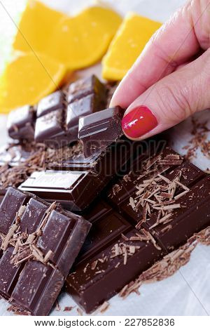 Tablet And Pieces Of Dark Chocolate With The Woman Finger