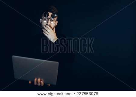 Young Man In Flip-up Glasses Holding Laptop Looking At It With Shock On Black Backdrop.