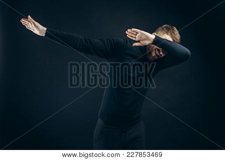 Anonymous Man In Black Stylish Outfit Covering Face With Hands Dancing On Black Backdrop.