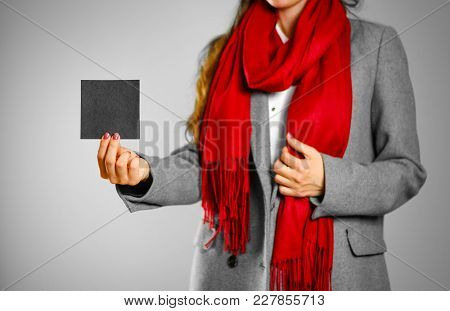 A Girl In Grey Coat And Red Scarf Holds A Black Clean Empty Square Sticker. Isolated On Grey Backgro