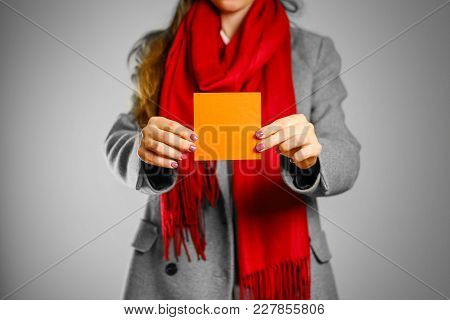 A Girl In Grey Coat And Red Scarf Holds A Orange Clean Empty Square Sticker. Isolated On Grey Backgr