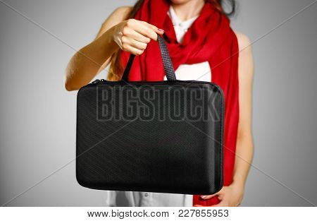 A Girl In A White T-shirt And Red Scarf Holds A Black Case. Isolated On Grey Background.
