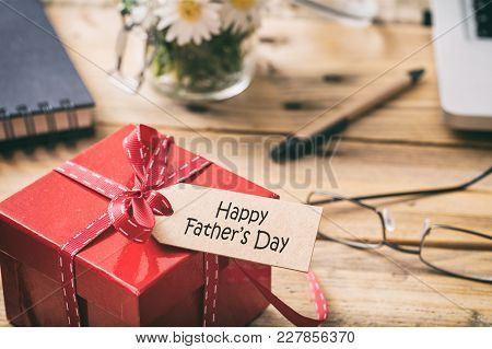 Father's Day. Red Gift Box With Happy Fathers' Day Tag, Blur Office Desk Background
