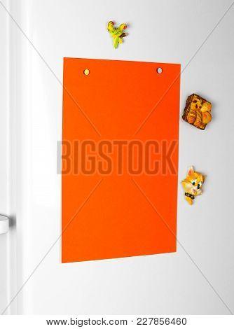 Orange Clean Blank A4 Sticker On The White Refrigerator. Close Up.