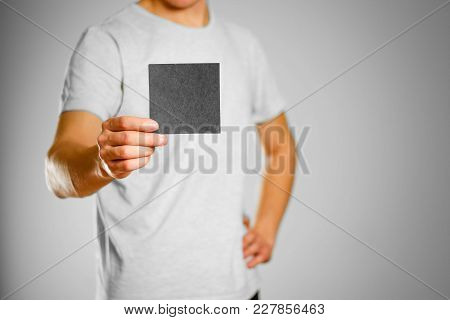 A Man In A Gray T-shirt Holds A Black Clean Empty Square Sticker. Isolated On Grey Background.