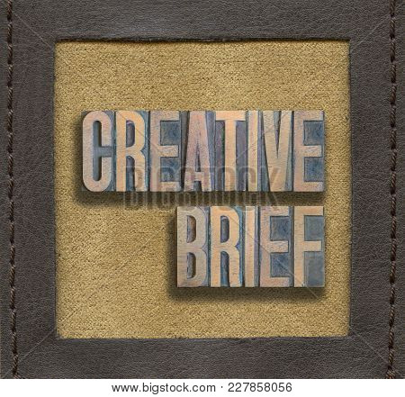 Creative Brief Phrase Assembled From Vintage Wooden Letterpress Inside Stitched Leather Frame