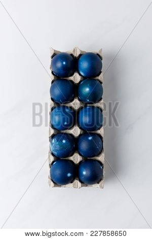 Top View Of Blue Painted Easter Eggs In Egg Tray On White Tabletop