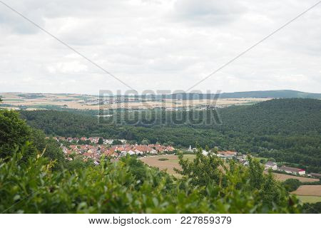 The Panoramic View From The Hill Of The Valley In German Countryside With A Small Town, Forests And