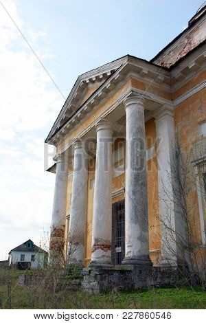 Old Orthodox Church In Classical Style With Classical White Portico And Yellow Shabby Walls And Cros
