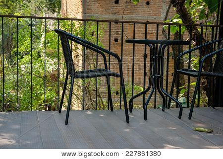 Black Table On Terrace Of House. Wicker Rattan Chair On Patio Near Garde At Home. Relax Lifestyle Co