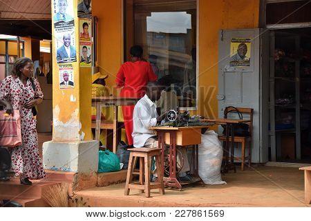 Kampala, Uganda - Aug 28, 2010: Shop Of A Tailor On A Suburban Street In Kampala. Unidentified Man W