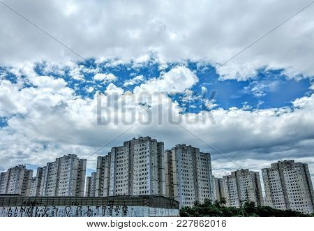 Comercial Buildings In An Urban City With Blue Sky And Heavy Clouds
