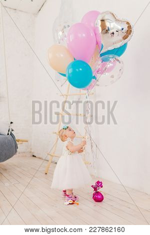 A Little Baby Girl In White Lavish Dress Is Standing In Living Room In The House Near The Decorative