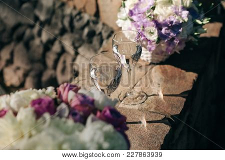 Two Glasses With Champagne On Stone Handrails Decorated With Flowers