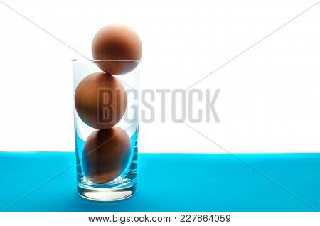 Three Brown Eggs In Transparent Glass On White Background.