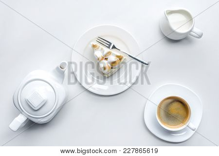 Top View Of Appetizing Piece Of Cake With Meringue, Teapot And Coffee On White Surface