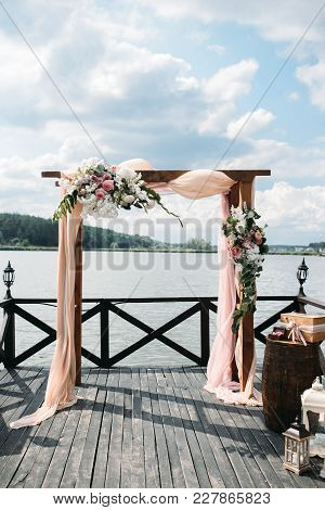 Wedding Arch Decorated With Flowers On The River Side