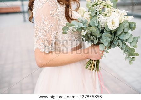 Bride's Hands With Wedding Bouquet