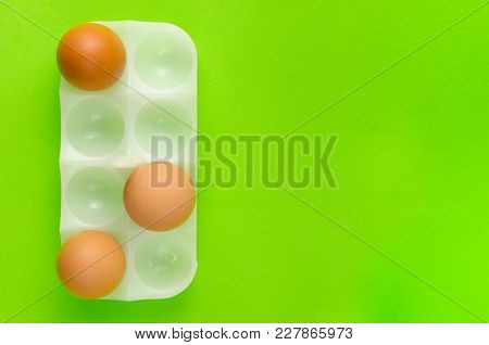 Three Brown Eggs In Stand For Egg A Bright Green Background.