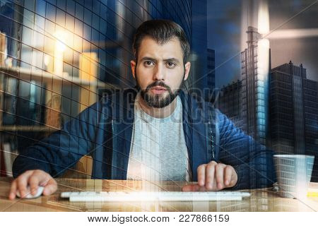 How Strange. Smart Attentive Young Man Looking At The Screen And Noticing Strange Facts While Sittin