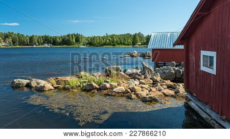 Fisherman Village In Sweden At Summer. View At A Swedish Village On A Lake With Houses Of Red Color.