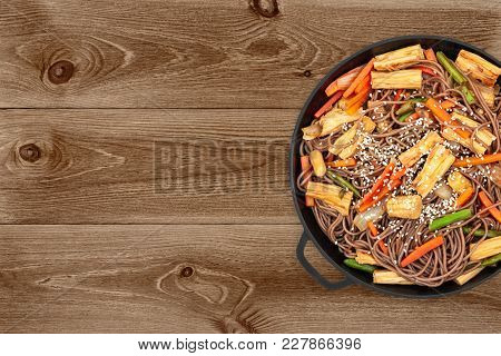 Delicious Soba With Tofu Skin And Vegetables In A Cast Iron Pan On Dark Wooden Background, Top View