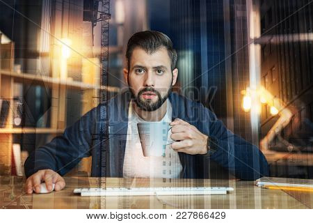 Attentive Look. Calm Enthusiastic Clever Worker Holding A Cup Of Tea And Looking Attentively At The