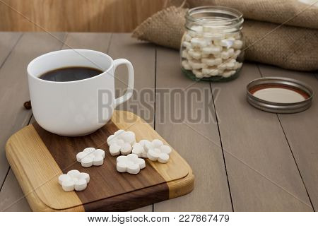 White Coconut Tapioca Cookies Spread On A Wooden Block With A Cup Of Black Coffee.