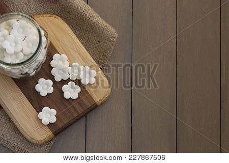 Overhead, Top-down Shot Of Some White Coconut Tapioca Cookies Spread On A Wooden Block And In A Glas