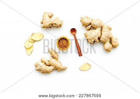 Seasoning. Ground Ginger In Small Bowl Near Sliced Ginger Root On Cutting Board On White Background