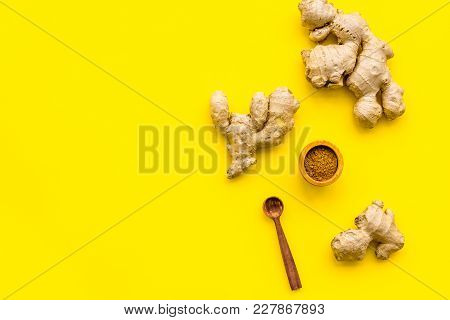 Seasoning. Ground Ginger In Small Bowl Near Ginger Root On Yellow Background Top View.