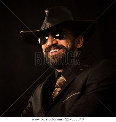 Portrait Of Smiling Elegant Handsome Man In Black Suit And Black Cowboy Hat On Black Background.