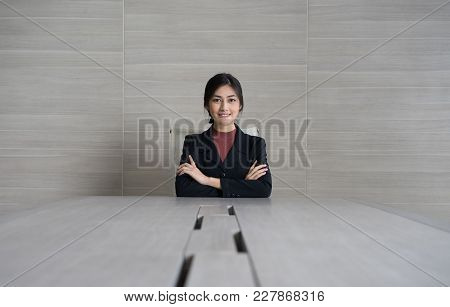 Portrait Of A Smiling Business Woman  Sitting At The Table In Office And Looking At Camera