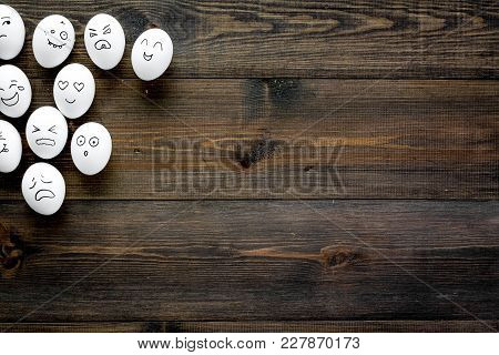 Emotions In Communication At Social Media. Faces Drawn On Eggs. Dark Wooden Background Top View
