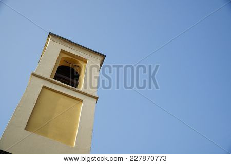 Bell Tower Of The Catholic Church Against Clear Blue Sky Bottom View.
