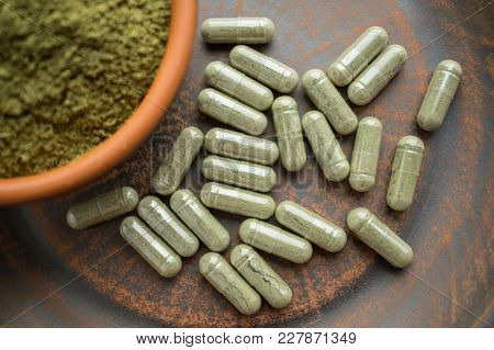 Supplement Kratom Green Capsules And Powder On Brown Plate. Herbal Product Alt-medicine Kratom Is Op
